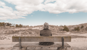 senior sitting on a bench looking at a deserted road