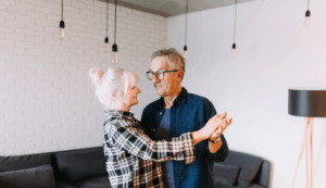 two older adults dancing in a living room