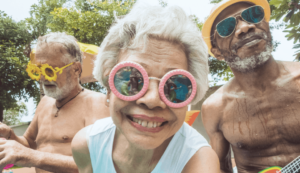 close-up of a senior lady with sunglassess smiling with two elderly men behind her