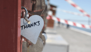 a padlock with thanks written on it attached to a fence