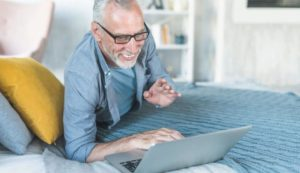 senior man laughing on the bed in front of a laptop
