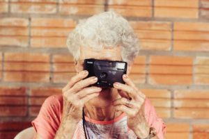 senior woman holding an old camera