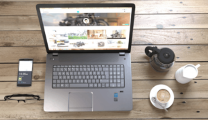laptop on a wooden table surrounded by a phone, coffee and milk