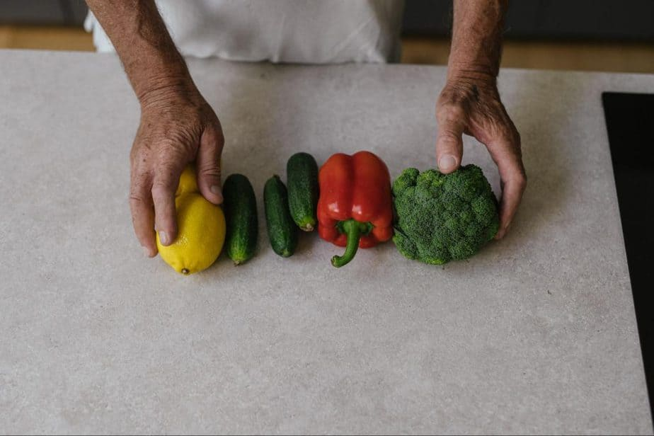 man holding vegetables on kitchen counter
