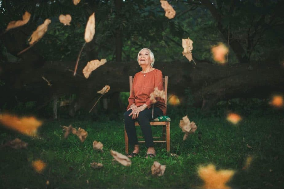 elderly woman sitting in nature surrounded by leaves