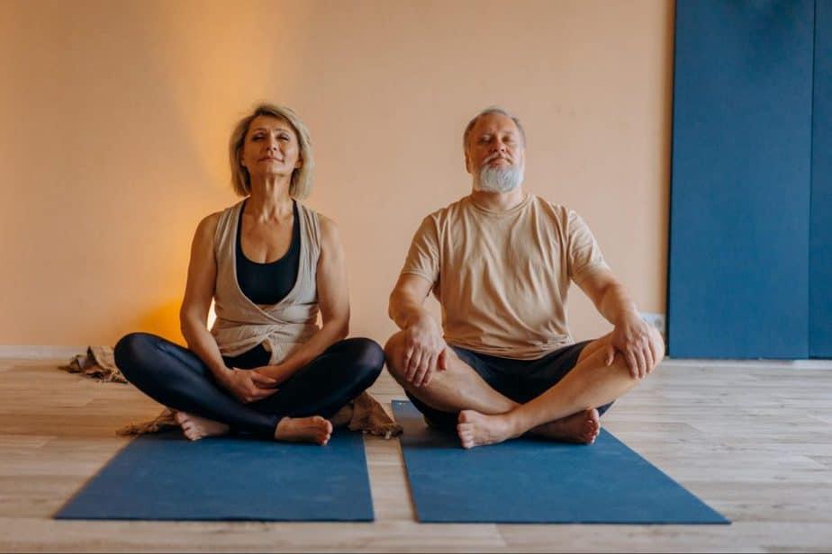senior couple meditating on yoga mats