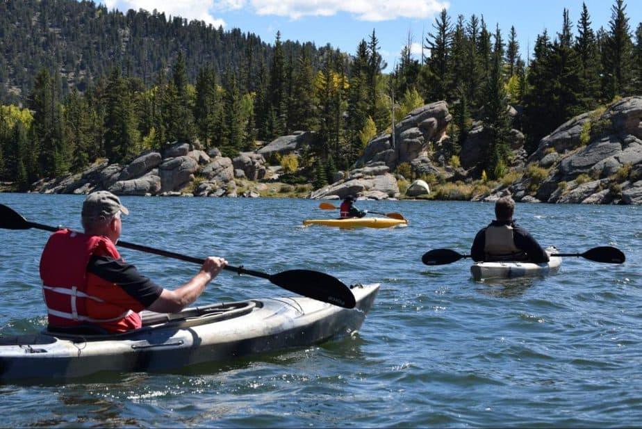 three men kayaking on a river