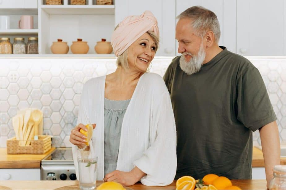 elderly couple preparing water with lemon in the kitchen