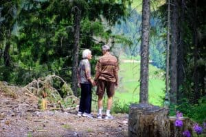 elderly couple walking in the forest