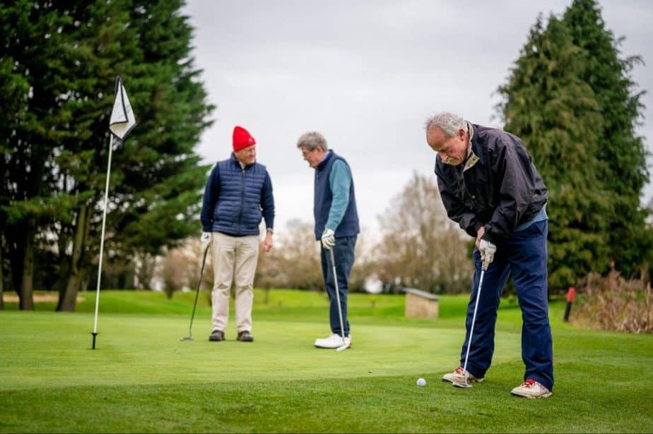 three older men playing golf
