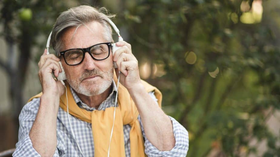 senior man dancing and listening to music on headphones