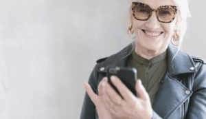 senior woman holding a phone and laughing