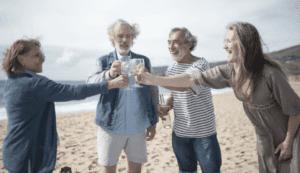 group of seniors toasting on a beach