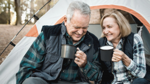 retired senior couple camping, drinking from cups, and laughing