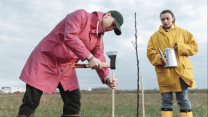 man in a red raincoat planting a tree while holding an axe with a woman in a yellow raincoat standing behind him, holding a watering can