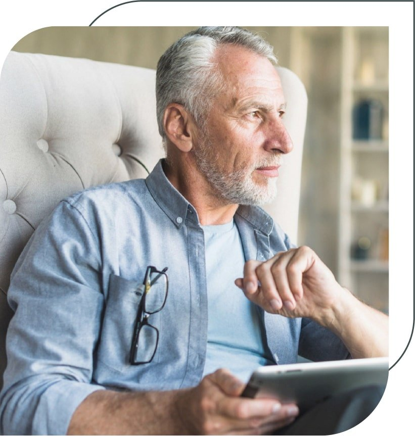 older man holding a tablet and thinking