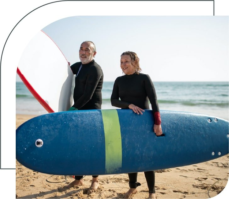 two seniors with paddle boards on a sandy beach