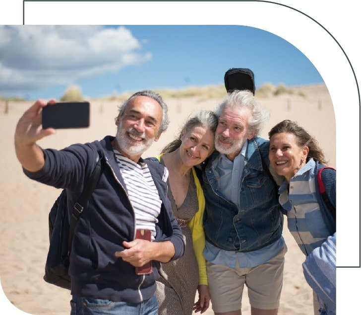 a group of four seniors taking a selfie on the beach