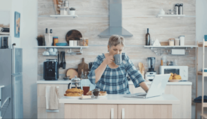 senior woman sipping out of a cup in a kitchen looking at a laptop