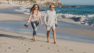 older man and woman walking on the beach