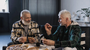 two male senior friends talking and eating pizza